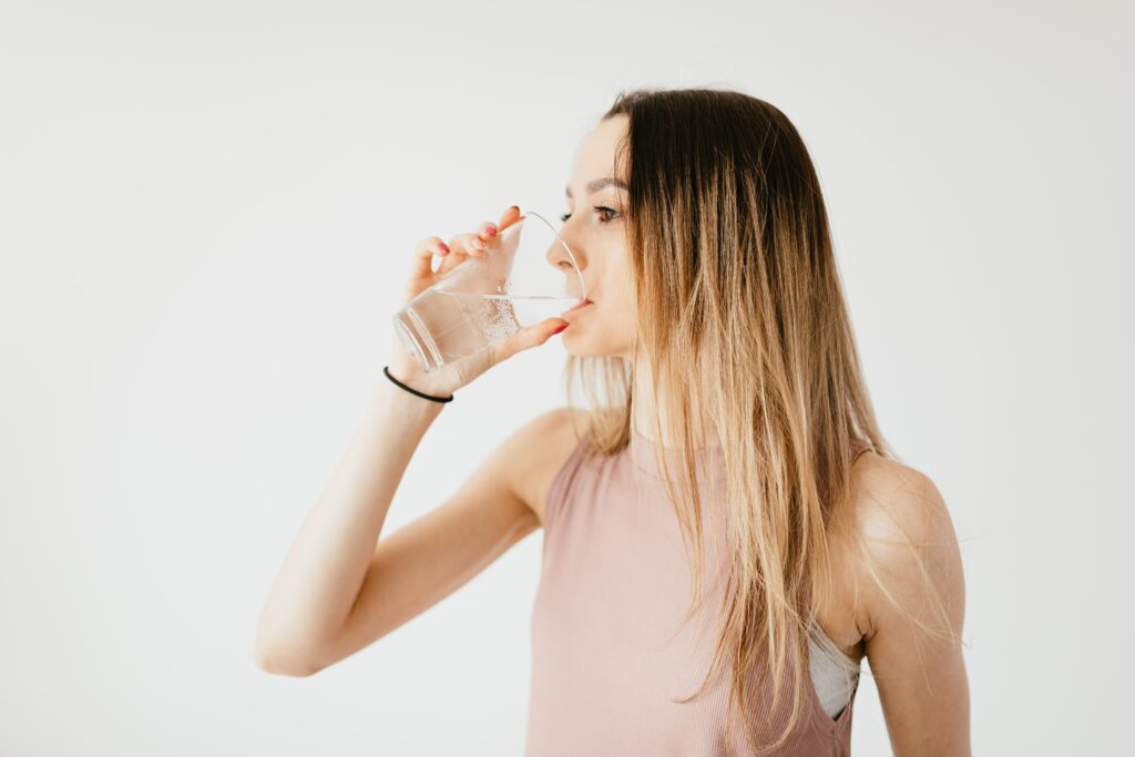woman drinking water from glass