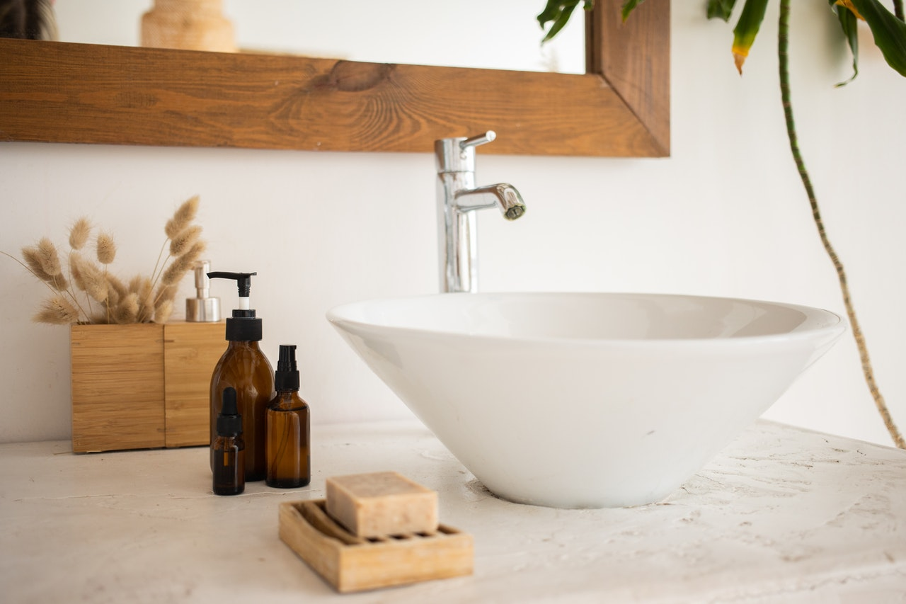 bathroom basin with essential oil bottles and soap