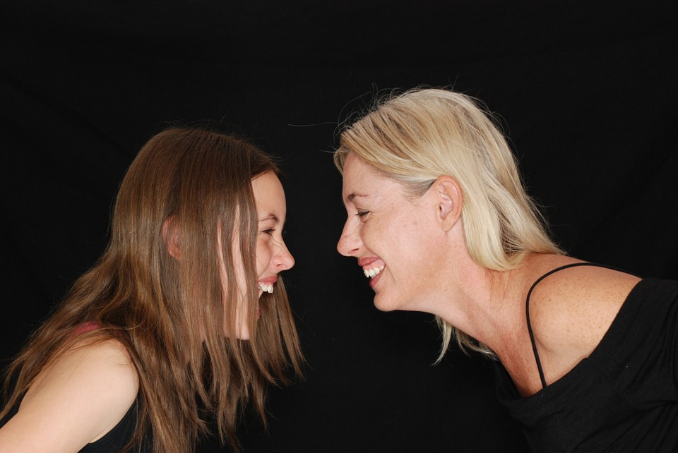 mom and teen daughter facing each other, laughing