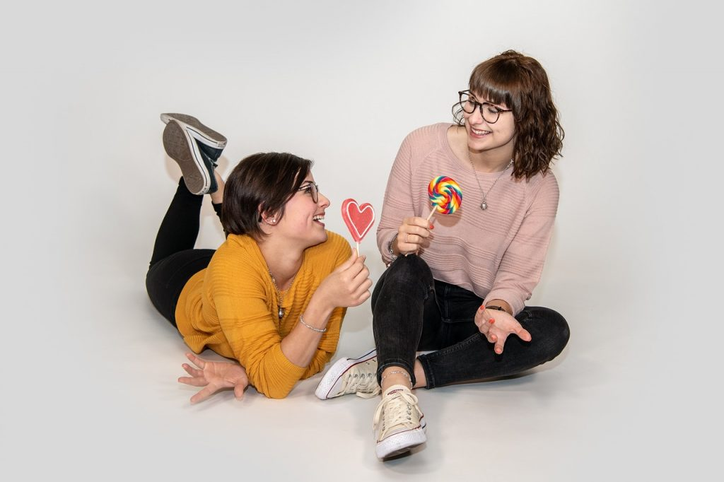 two teens eating lollipops and happy